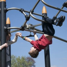Standing Girl and Hanging Boy playing on Proludic Play Equipment
