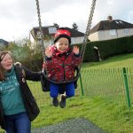 HarpendenTownCouncil Picture 8 parent pushing smiling child on swing no hands example of proludic play equipment