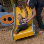 smiling child playing with parent on example of Proludic children's play equipment