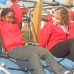pair of girls playing on Proludic example of school play equipment
