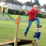 harpendon site play area image 2 boy leaping on adventure play play equipment