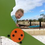 smiling child on Proludic play equipment slide against blue sky