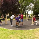range of outdoor gym equipment proludic in use by young adults in outdoor green space