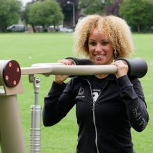 closer crop image of woman using urbanix proludic outdoor gym at jubilee park in knowsley