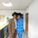 Proludic Staff Dressed Up in Festive Corresponding Suits Red Green and Blue